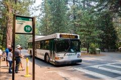 公车运送穿梭游人在位于优胜美地国家公园的各种各样的兴趣点之间 免版税库存图片