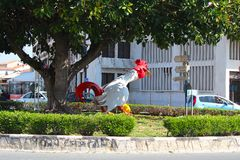 公鸡雕塑和非常老大树在利马索尔广场,塞浦路斯 库存图片