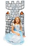 公主礼服的女孩在纸板城堡附近坐 免版税库存照片