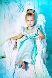 公主礼服的小女孩在冬天神仙的背景 免版税库存照片