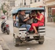六个人加冠入小摩托车驾驶的出租汽车 免版税库存照片