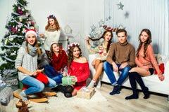六个女孩和人公司在圣诞树附近 免版税库存图片