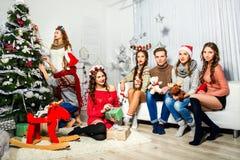 六个女孩和人公司在圣诞树附近 图库摄影