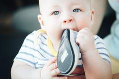 六个月是的婴儿小儿童男孩采取他的在嘴的鞋子 库存照片