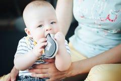 六个月是的婴儿小儿童男孩采取他的在嘴的鞋子 库存图片