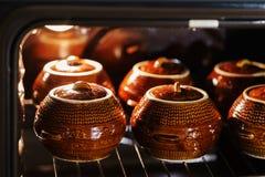 六个热的棕色黏土陶瓷罐用在烤箱里面的支持的或被炖的食物 库存图片