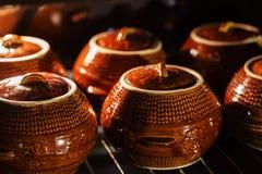 六个热的棕色黏土陶瓷罐用在烤箱里面的支持的或被炖的食物 库存照片