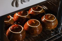 六个热的棕色黏土陶瓷罐用在烤箱里面的支持的或被炖的食物 图库摄影