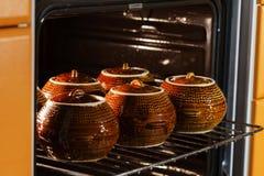 六个热的棕色黏土陶瓷罐用在烤箱里面的支持的或被炖的食物 免版税库存图片