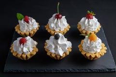 六个蛋糕用蛋白质在黑暗的石板材的奶油和夏天莓果 库存图片