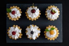 六个蛋糕用蛋白质奶油和夏天莓果 免版税图库摄影
