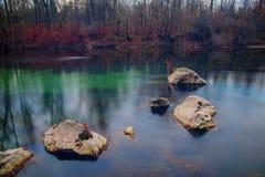 六块石头在一条缓慢流动的河 免版税图库摄影