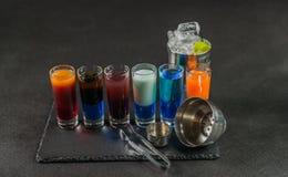 六份不同色的射击饮料,排队在黑石头pla 免版税库存图片