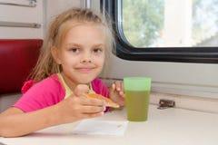 六年女孩饮用的茶用在火车的一个三明治在船外第二等的支架的桌上 库存图片