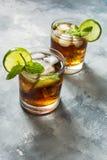 兰姆酒和可乐 与石灰和冰的古巴Libre饮料在土气具体桌上 库存照片