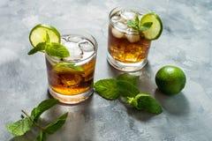 兰姆酒和可乐 与石灰和冰的古巴Libre饮料在土气具体桌上 免版税图库摄影