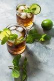 兰姆酒和可乐 与石灰和冰的古巴Libre饮料在土气具体桌上 图库摄影