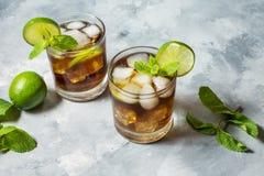 兰姆酒和可乐 与石灰和冰的古巴Libre饮料在土气具体桌上 免版税库存照片