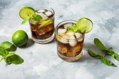 兰姆酒和可乐 与石灰和冰的古巴Libre饮料在土气具体桌上 库存图片