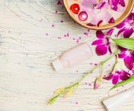 兰花、奶油和化妆水用水在白色破旧的别致的背景,顶视图滚保龄球 免版税库存图片
