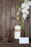 兰花和蜡烛在木背景 免版税库存照片