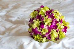 兰花花束在一张白色床上的 免版税库存图片