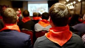 共产主义者的会议作早期工作在Komsomol -红色领带的听众细听告诉并且显示介绍的讲师 股票视频