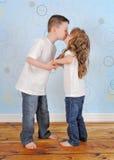 共享姐妹年轻人的可爱的兄弟亲吻 免版税库存图片