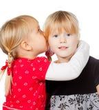 共享秘密的小女孩 库存照片