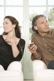 共享耳机的成熟夫妇。 免版税库存图片