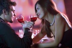 共享酒年轻人的celebrat夫妇玻璃红色餐馆 免版税库存图片