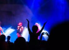 共同安排出席音乐会,剪影是可看见的人们的人群,由后照由阶段光 被举的手和巧妙的电话是visi 免版税库存照片