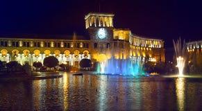 共和国正方形在晚上在耶烈万 澳洲市时钟大厅找出珀斯西部塔的城镇 有色的光的一个喷泉和光照亮的大厦 库存图片