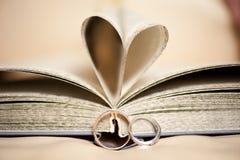 关于一本开放书的婚戒与以心脏的形式页 免版税库存图片