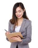 关于剪贴板的亚洲女实业家摘记笔记 免版税库存图片