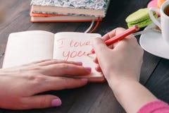 关于在笔记本写的爱的词组 背景蓝色框概念概念性日礼品重点查出珠宝信函生活纤管红色仍然被塑造的华伦泰 免版税库存图片