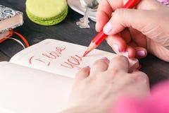 关于在笔记本写的爱的词组 背景蓝色框概念概念性日礼品重点查出珠宝信函生活纤管红色仍然被塑造的华伦泰 免版税库存照片