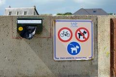 关于墙壁的旅游讯息在显示狗和狗在皮带唯一的标志的海滩在公开狗屎袋子分配器旁边 免版税库存图片