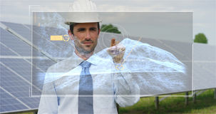 关于太阳光致电压的盘区,用途的一位未来派工程师专家与遥控的一张全息图,进行复杂行动对monito 免版税图库摄影