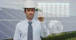 关于太阳光致电压的盘区,用途的一位未来派工程师专家与遥控的一张全息图,进行复杂行动对monito 免版税库存图片
