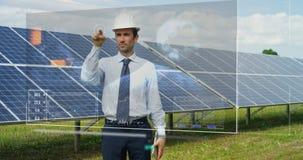 关于太阳光致电压的盘区,用途的一位未来派工程师专家与遥控的一张全息图,进行复杂行动对monito 库存图片