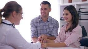 关于妇女健康,有好消息的医生的交谈坐在一间医疗屋子的愉快的夫妇的 股票视频
