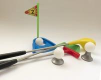 关于教高尔夫球比赛的背景与玩具高尔夫俱乐部a的 库存照片