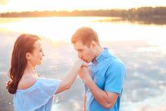 关于日落的结婚提议 年轻人提出提案订婚给他的女朋友在海滩 免版税库存照片