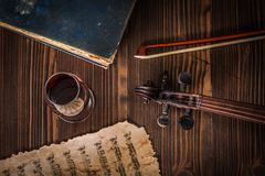 关于旧书、小提琴纸卷、弓和乐谱的顶视图 库存照片