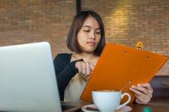 关于本文的亚洲短发妇女读书财务报告 库存照片