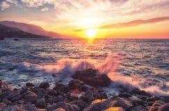 关于石头的波浪断裂在日出 免版税图库摄影