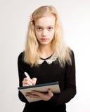 关于笔记薄的白肤金发的青少年的女孩文字笔记 库存照片