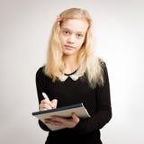 关于笔记薄的白肤金发的青少年的女孩文字笔记 图库摄影