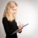 关于笔记薄的白肤金发的青少年的女孩文字笔记 免版税库存照片